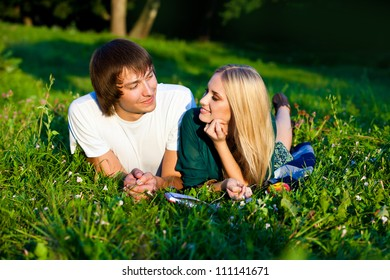 couple lying on the grass in the park. They smile and look at each other