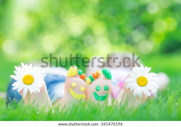 Couple lying on green grass. Children having fun outdoors in spring park