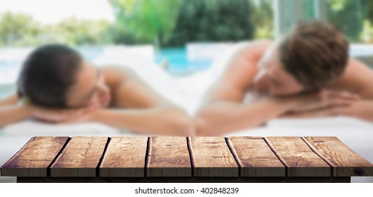 Couple lying on massage table at spa center against wooden floor