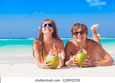 couple lying on a tropical beach in Barbados and drinking a coconut cocktail