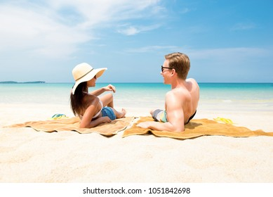 Couple lying on white sand beach relaxing and taking a sunbath in summer at Koh samui island, Thailand
