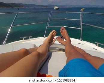 Couple lying on white yacht. Luxury vacation on yacht on the island