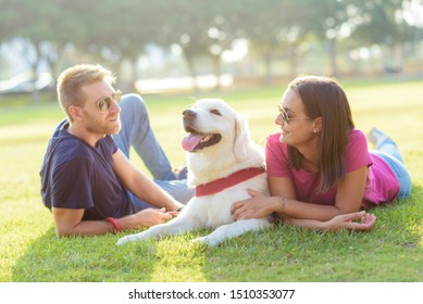 Couple lying in the park while having fun with the dog.happy family concept