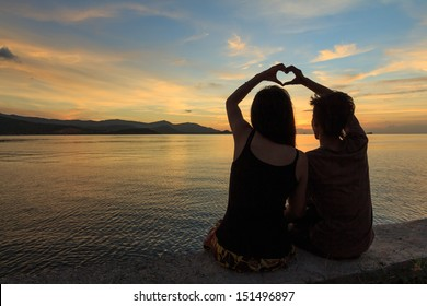 couple makes heart symbol at dusk