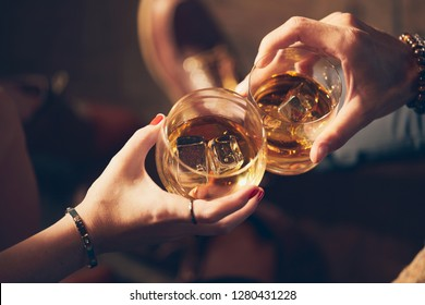 A couple makes a toast with two glasses of whiskey