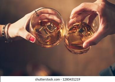 A couple makes a toast with whiskey
