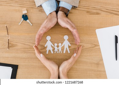 Couple making circle with hands on wooden table with paper people inside, family insurance