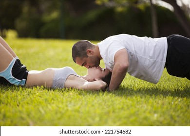 Couple making exercise and kissing at the city park
