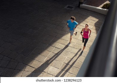 Couple making fitness and jogging in the urban area of the city. High angle view of two mature people training together on road. Fitness man and woman running on city street.