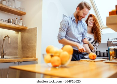Couple making fresh organic juice in kitchen together