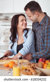 Couple making fresh organic juice in kitchen together. A young woman in a blue shirt slices a baguette. A man is hugging his girlfriend in a white kitchen. Romantic concept