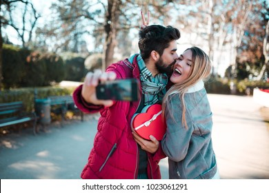 Couple making selfie. Man surprising his girlfriend with a gift. Couple in love. Valentine's day.