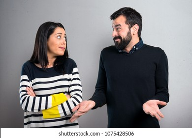 Couple making unimportant gesture on grey background