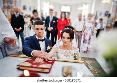 Couple making vows during their wedding ceremony in the church with the guests standing behind.
