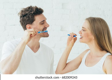 Couple man and woman clean teeth with tooth brush