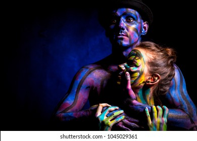 Couple of man and woman. Face art. Portrait of lovers in paint.  Passion make up. Dark background.
