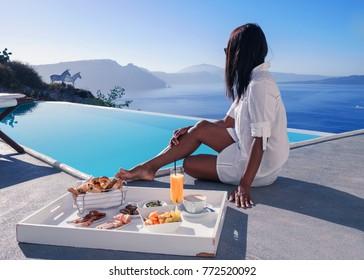 Couple man and woman having breakfast by the swimmingpool at an luxury resort Santorini Oia Greece with a look over the Caldera ocean Santorini Island