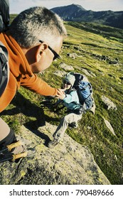 Couple Man and Woman help giving hands climbing rocky mountains Love and Travel Lifestyle concept hiking adventure vacations outdoor