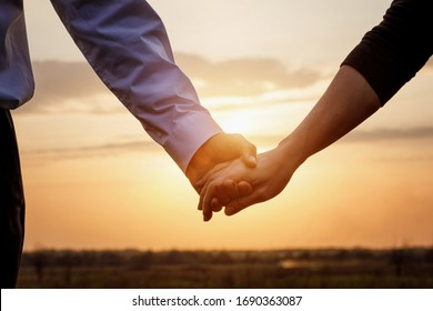 Couple man and woman hold hands on sunset background.