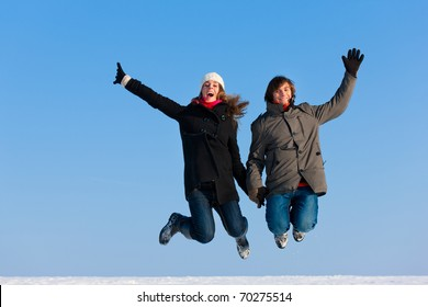 Couple - man and woman - jumping high on a winter day