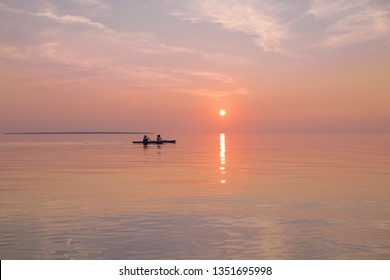Couple man and woman kayaking paddling at sunset hour on a tranquil lake surface. Lake Superior Provincial Park, Canada, Ontario. Active lifestyle, outdoor living, camping, travel, explore concept.