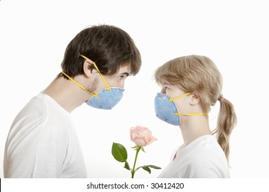 Couple, man and woman in masks  face to face looking over rose flower ,  against white background