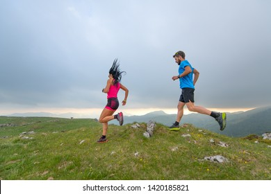 Couple of man and woman mountain athletes runners in action