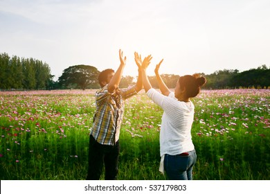Couple of man and woman in the park or garden or field doing hi five with both hands represent successful,  achievement and motivation at dusk or dawn.