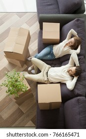 Couple man and woman sitting on sofa in living room hands behind head, happy young homeowners relaxing on couch after packing boxes, easy relocation with moving delivery service concept, top view