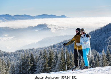 Couple, man and woman skiers standing on the background of mountains and valley