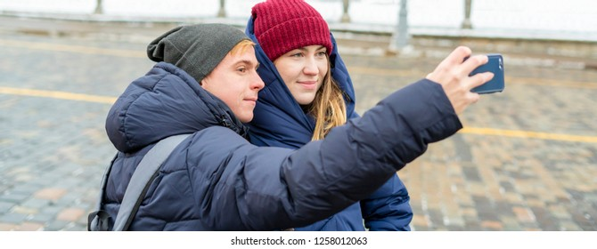 couple of man and woman taking a self portrait outdoors in the street on a winter day