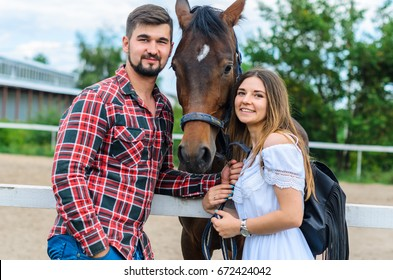 couple man and woman walking on a ranch in the background of thoroughbred horses. girl in a white dress , a guy dressed as a cowboy. people are happy and having a good time.