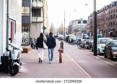 A couple (man and woman) man is walking in the street in Amsterdam