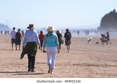Couple man and woman wearing hats on the pedestrian walk along the sandy shores of the Pacific Ocean in the crowd of other people inhale the fresh scent of sea air - a great healthy lifestyle.