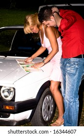 couple with map looking for direction infront their car