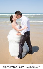 couple of married lovers embraces on the beach in wedding clothes