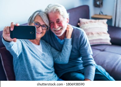 couple of mature people having fun at home sitting on the sofa taking a selfie together smiling and looking at the phone - two retired pensioners enjoying the technology indoors