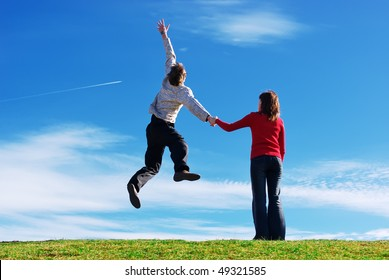 Couple in meadow. Man jump to the sky. Conceptual design.