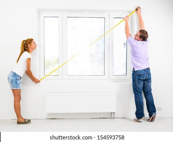 couple is measuring their new empty apartment