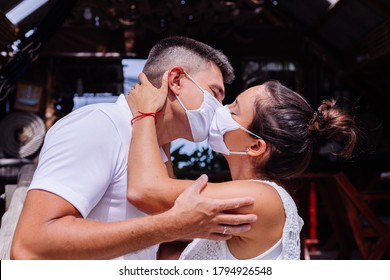 Couple in medical white face masks on vacation stand outside hotel and kissing.