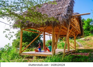 Couple meditating at bamboo eco retreat hotel. Yoga studio with a view of the ocean. Shot in beach town, Montanita, Ecuador.