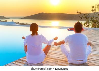 Couple meditating together at sunrise