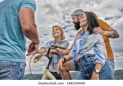 Couple meet cheerful friends with bicycle during walk. Cycling modernity and national culture. Company stylish young people spend leisure outdoors sky background. Group friends hang out with bicycle.