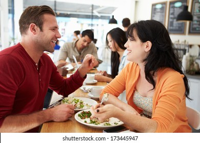 Couple Meeting For Lunch In Busy Cafe
