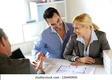 Couple meeting real-estate agent to buy property