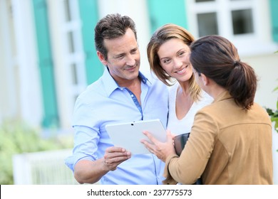 Couple meeting real-estate agent outside new property