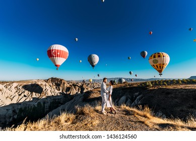The couple meets the dawn. The man proposed to the girl. Family trip to Turkey. Couple at the balloon festival. Couple travels the world. Holidays abroad. The Landscapes Of Cappadocia