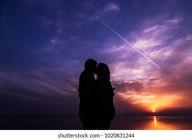 couple meets the sunset by the water