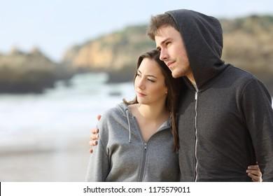 Couple of melancholic teens contemplating ocean walking on the beach