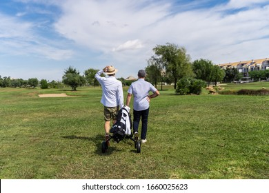 Couple of men in hats walking on a golf course with a cart to carry the equipment surrounded by buildings and trees